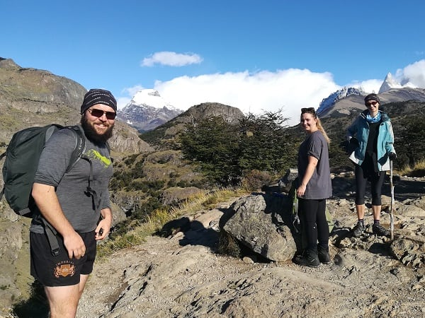 Three hikers with views of glaciers and mountains in the background.
