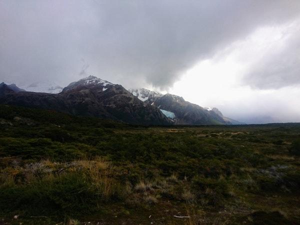 Views of a glacier across grassland.