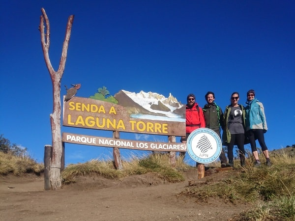 A sign reading senda a laguna torre, plus the hikers.